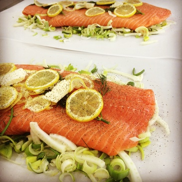 Salmon En Papillote - a parchment paper wrapped salmon fillet on a bed of leeks, fennel, white wine , dill and lemon.